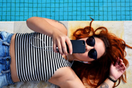 An image of a woman near a pool on her smartphone